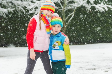 Kids in colorful clothes playing in the park under snowfall, wearing colorful knitwear.