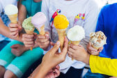 6 corns of colorful ice cream holding by kids