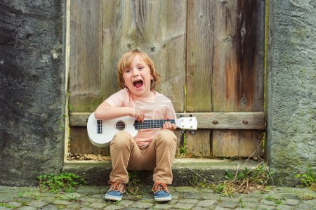 Photo for Little happy boy plays his guitar or ukulele - Royalty Free Image