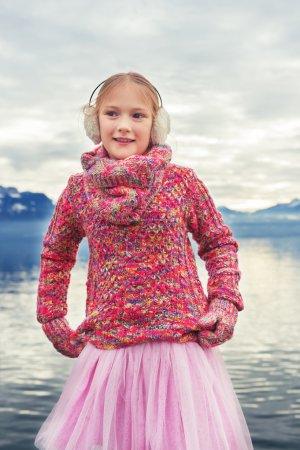 Photo pour Outdoor close up portrait de petite fille adorable d'enfant de 8 ans de repos au bord du lac de Genève sur une belle journée d'hiver, portant pull rose coloré et chaleureux earmuffs - image libre de droit