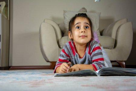Photo pour Petite fille avec un livre devant elle tout en étant couchée sur le sol et en regardant ailleurs - image libre de droit