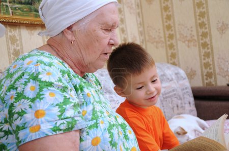 Grandmother and grandson reading book