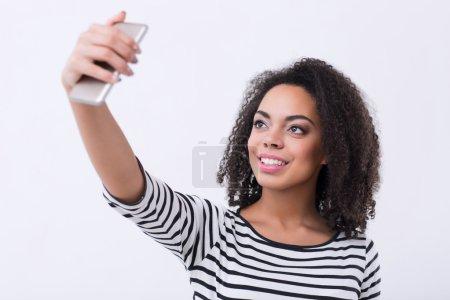 Photo pour Dis juste du fromage. contenu gai mulâtre femme tenant téléphone portable et faire des selfies tout en exprimant la positivité - image libre de droit