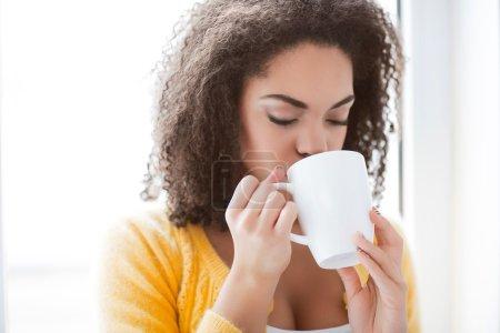 Pleasant mulatto woman drinking tea