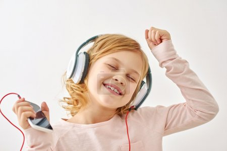 Happy girl dancing while listening to music