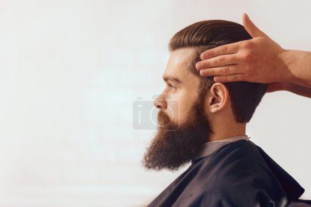 Foto de Mira seguro. Hombre guapo con barba sentado en la peluquería mientras el peluquero profesional peinar su cabello - Imagen libre de derechos