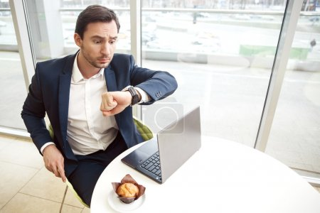 Surprised businessman looking at his wristwatch