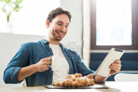 Photo for Have some fun. Delighted smiling  man using tablet and drinking coffee while sitting at the table in the cafe - Royalty Free Image