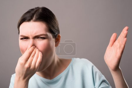 girl closing her nose and expressing disgust