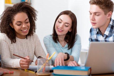 Photo pour Un moment d'étude. Étudiants positifs et enchantés assis ensemble à la table et écrivant quelque chose pendant leurs études - image libre de droit