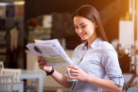 Positive woman reading newspaper