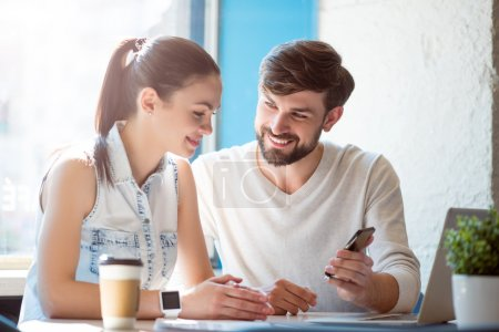 Photo for Look here. Positive and cheerful modern young woman and man using a smartphone and a laptop sitting in a cafe and drinking coffee - Royalty Free Image