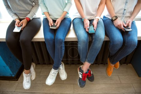 Photo pour Using mobile phones. Cropped picture of four modern young women using their mobile phones while sitting on a window sill - image libre de droit