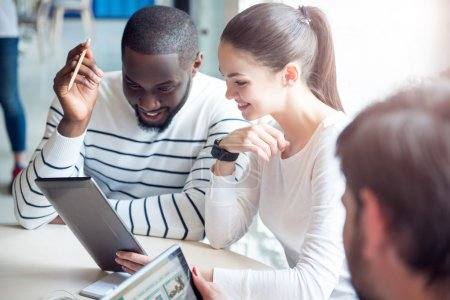 Photo for Business colleagues. Cheerful and smiling young people sitting together and using a digital tablet while discussing their business project - Royalty Free Image