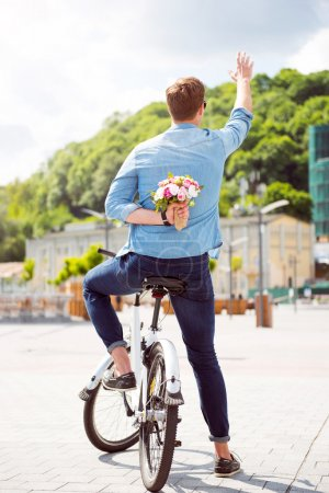 Man holding flowers behind his back