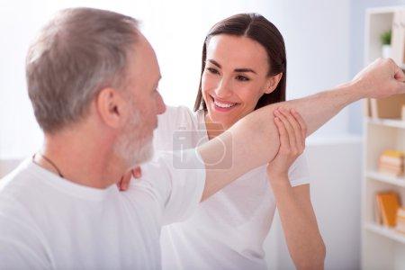 Photo pour Assistance infirmière. Kinésithérapeute souriant et ravi examinant une main d'homme dans le bureau médical - image libre de droit