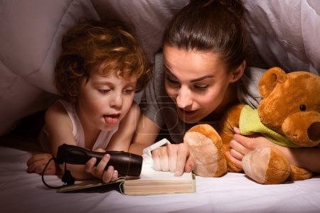 Mother and child reading book under blanket