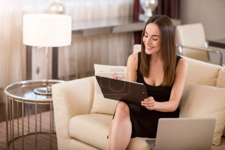 Photo for Nice work. Happy beautiful young woman looking down and taking notes while sitting on the sofa near an open laptop - Royalty Free Image