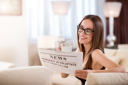 Woman having drink and reading news