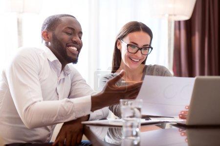 Photo pour C'est un succès. Belle femme et homme afro-américain content regardant les papiers et se réjouissant du succès de leur travail - image libre de droit