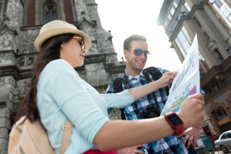 Cheerful tourists using city map