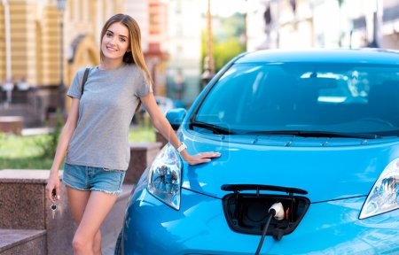 Woman standing near electric car