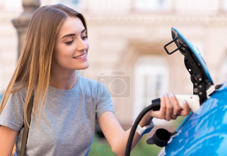Woman charging battery of eco car