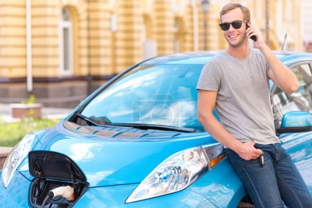 Man talking on smartphone near eco car