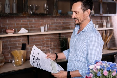 Man reading newspaper in the kitchen