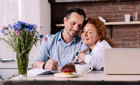 Woman cuddling man while sitting in kitchen