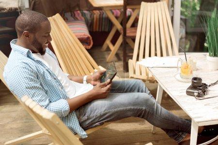 Foto de Comparte tus emociones. Alegre guapo encantado hombre sentado en la silla y el uso de la tableta mientras descansa en casa - Imagen libre de derechos