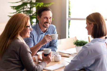 Photo for Refresh your mind. Positive delighted smiling colleagues having a nice conversation and finishing lunch while sitting at the table - Royalty Free Image