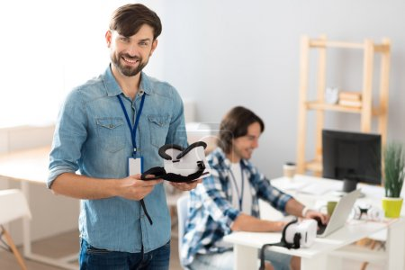 Cheerful smiling man holding virtual reality device