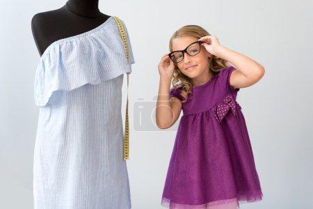 kleines Mädchen setzt Brille auf
