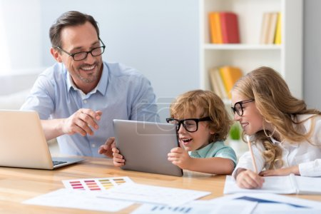 Photo pour It is amazing. Smiling man and lovely children with glasses looking with interest at the tablet while sitting at the table - image libre de droit