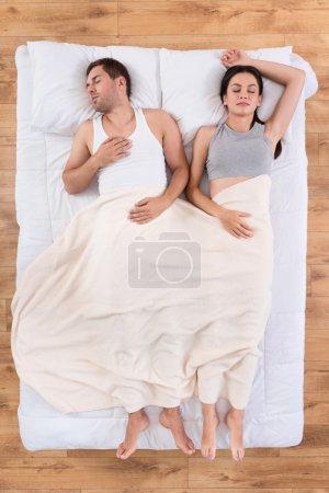 Young man and woman sleeping together in bed