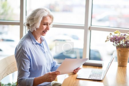 Pleasant content senior woman sitting at the table