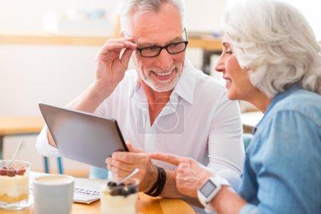 Photo pour Heureux ensemble. Couples aînés heureux heureux souriants et utilisant la tablette tout en se reposant dans le café - image libre de droit