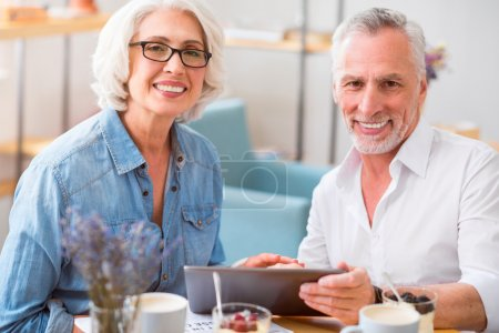 Cheerful smiling couple resting in the cafe