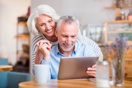 Cheerful couple using tablet