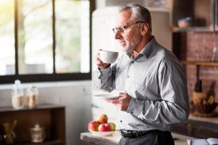 Senior businessman having coffee in kitchen at home