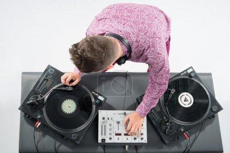 Photo for Top view portrait of emotional handsome dj, stylish look and haircut with headphones spinning vinyl records on turntable isolated on white background - Royalty Free Image