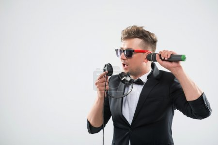 DJ in tuxedo having fun talking into headphones and listening mi