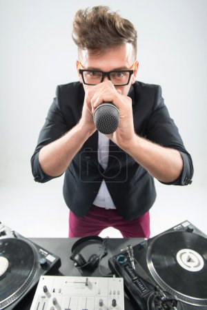 DJ in tuxedo holding microphone and headphones