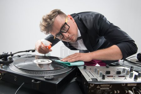 DJ in tuxedo cleaning his turntable