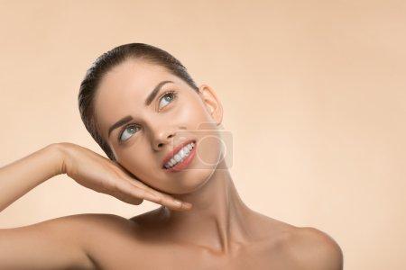 Photo pour Portrait de beauté visage de belle fille avec une peau propre et fraîche à la recherche de côté heureux souriant et toucher son visage isolé sur fond beige avec lieu de copie - image libre de droit