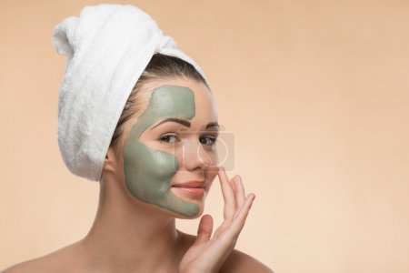 Spa girl with a  towel on her head applying facial clay mask and