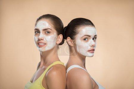 Girls applying facial cream mask