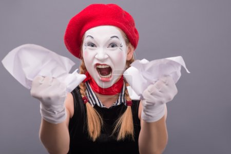 Female mime angry crumpling a paper