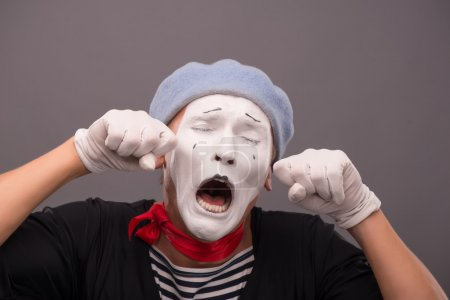 Photo pour Gros plan Portrait de jeune mime mâle au visage blanc, chapeau gris pleurant, criant et essuyant ses larmes isolées sur fond gris avec lieu de copie - image libre de droit